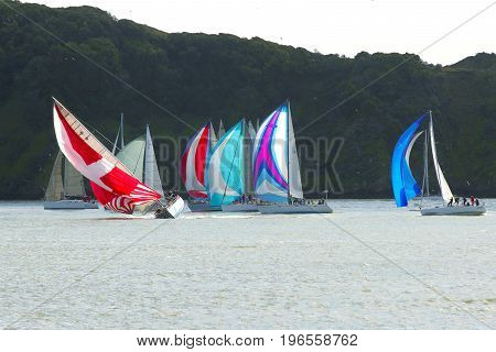 Sailboat race with one boat heeling, clear sky with dark land behind boats.
