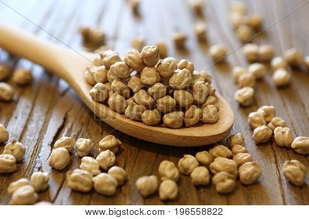 Dry and uncooked chickpeas in spoon and scattered on wooden background