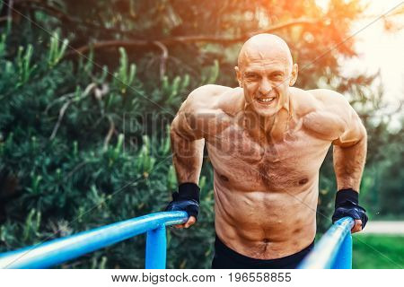 Man doing push ups on parallel bars in a park