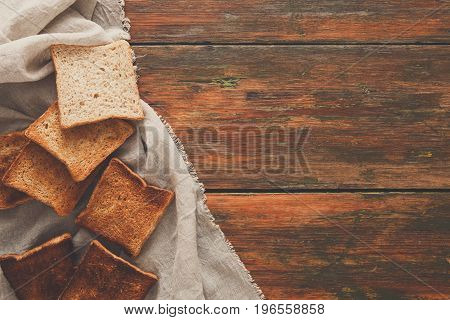 Toasted slices of white bread on sackcloth on rustic wooden table. Still life, top view, copy spase, bakery and grocery background