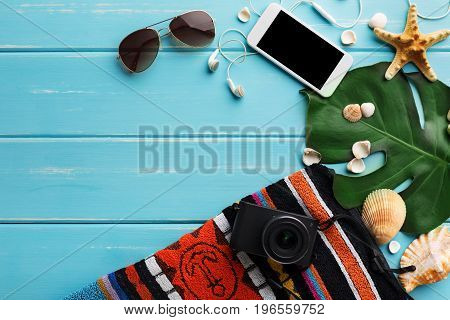 Vacation background on blue wood, top view. Beach accessories, sunglasses, photo camera, smartphone and seashells