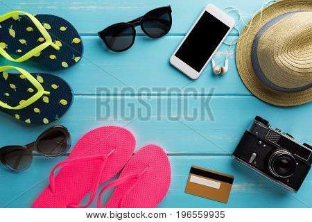Vacation background on blue wood, top view with copy space. Retro photo camera, flip flops, sunglasses and straw hat. Online shopping on smartphone.