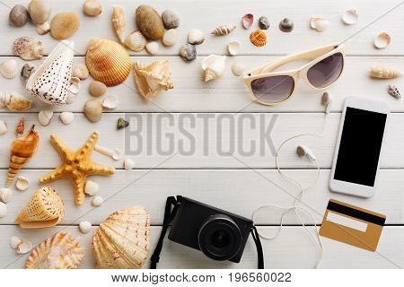 Vacation background on white wood, top view with copy space. Sunglasses and photo camera. Booking tickets online on smartphone.