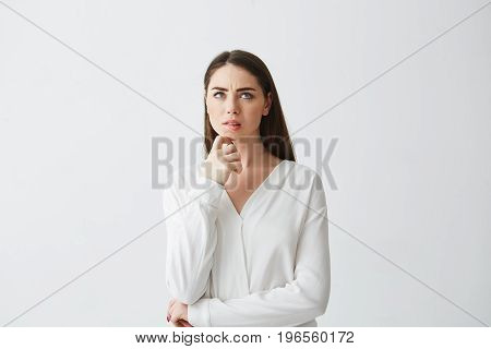 Portrait of young beautiful brunette businesswoman dreaming thinking frowning over white background. Hand on chin. Copy space.