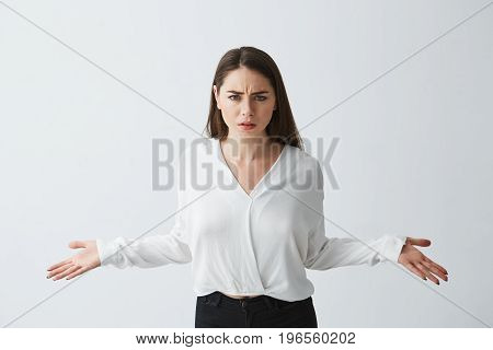 Portrait of displeased young businesswoman spreading hands out looking at camera over white background. Copy space.
