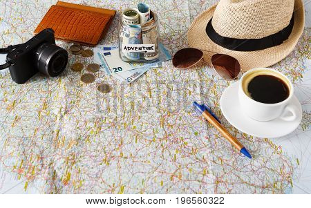 Summer vacation planning background. Preparing tourist stuff for a trip and drinking coffee. Essential things for traveller on the map. Tourism and vacation concept, copy space
