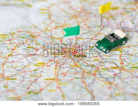 Travelling to France by car background. Visited cities tackled with flag-pins on the map. Vintage car on atlas. Tourism, vacation and busines trip concept, closeup, copy space