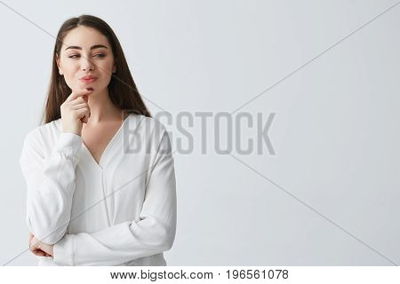 Young beautiful playful businesswoman with cunning tricky glance smiling over white background. Copy space.