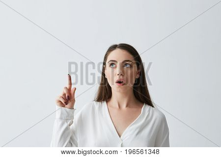 Surprised young beautiful businesswoman with opened mouth pointing finger up over white background. Copy space.