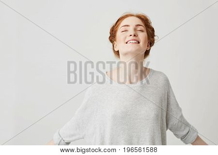 Portrait of young happy redhead girl smiling with closed eyes over white background. Copy space.