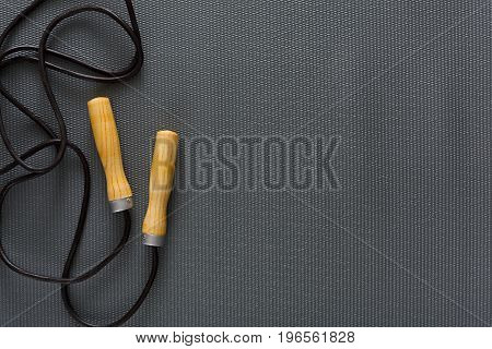 Top view of jump rope on black background. Skipping rope, fitness supply, weightloss, slimming concept