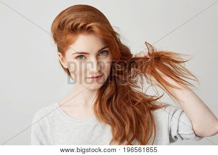 Close up of young beautiful ginger girl looking at camera smiling touching hair over white background. Copy space.