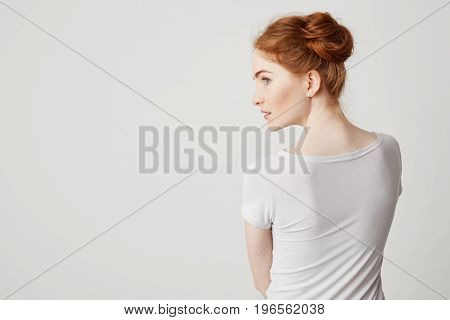 Portrait of young redhead girl with buns standing back to camera looking in side over white background. Copy space.