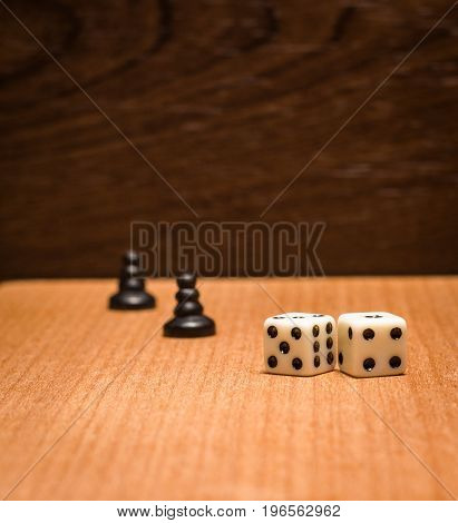 Pawns and dice for logical board games on a wooden background are small plastic objects