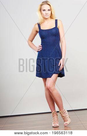 Summer trendy fashionable outfit ideas concept. Blonde attractive woman wearing short blue cocktail dress and fancy high heels.