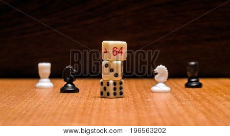 Dice and chess pieces on a wooden background objects for the most popular logical and gambling board games