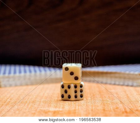 Dice and two half of a card deck on a wooden background objects for table games that are played around the world