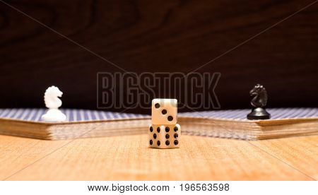 Dice card deck and chess horses on a wooden background objects for popular logical and gambling board games developing thinking