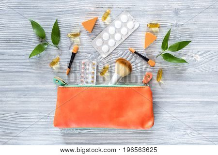 Cosmetic bag with contraceptives and pills on wooden table background top view.