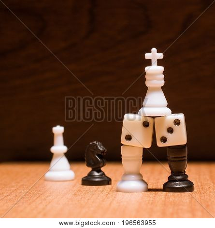 White chess king rises above his guards on a wooden background standing on dice and rooks