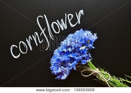 blue cornflowers bouquet, tied up with flax rope, over chalkboard, written name of a flower