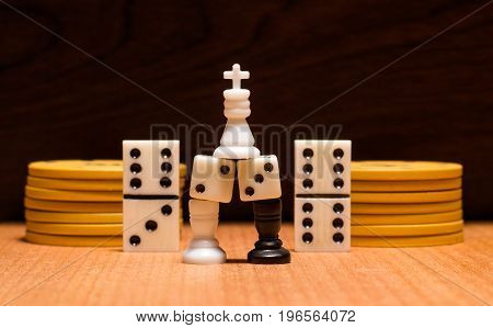 Objects for the most popular board games on a wooden background chess pieces dice poker chips and dominoes