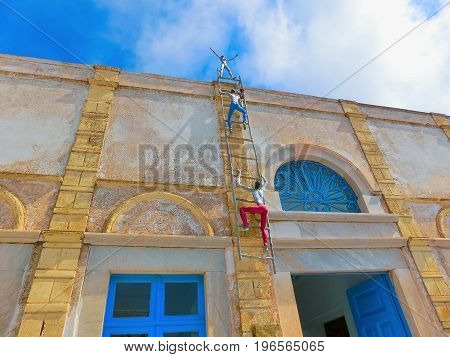 Oia, Santorini, Greece - June 10, 2015: Sculpture of climbing men as decoration of old building in Oia town, Santorini island Oia is a very popular city among tourists on Santorini island