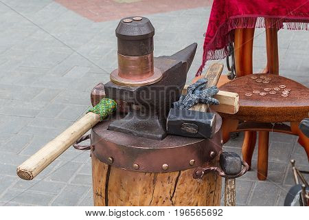 Coinage manually. Sledgehammer, anvil, used for minting coins. Coins scattered on the surface. Handmade.