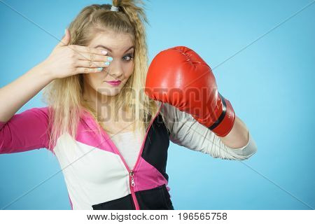 Funny blonde girl female boxer in big fun red gloves playing sports boxing studio shot on blue