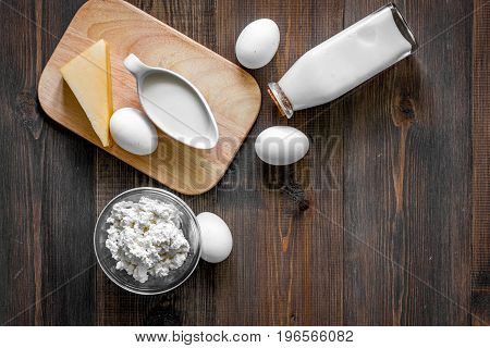 Farm products. Milk, cottage, eggs on dark wooden background top view.