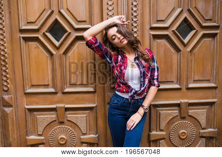 Portrait Of Cute Smiling Woman On A Background Of Braun Vintage Door Wearing Casual Clothes In Summe