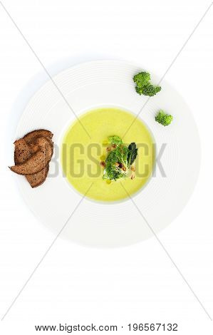 Green Cream Soup Of Broccoli And Croutons Close-up In A White Plate..