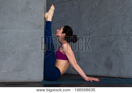 Young Caucasian girl doing upward facing forward bend exercise against the wall during yoga class in studio.