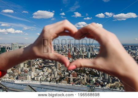 Female hands In form of heart against Tokyo Tower with skyline in Tokyo Japan. Focus on the tower.