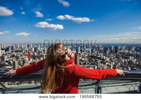 Happy young woman looking at Tokyo from rooftops. Girl stands with her back. Tokyo Tower with skyline on background.