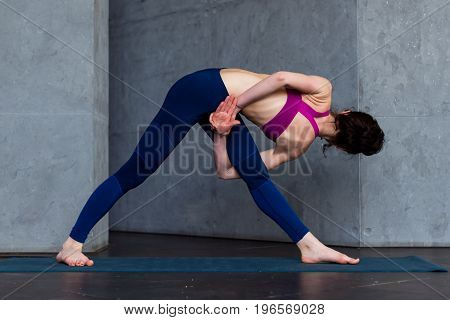 Rear view of young female yogi in sports bra and leggings doing bound extended side angle pose, baddha utthita parsvakonasana, while practicing yoga indoors.