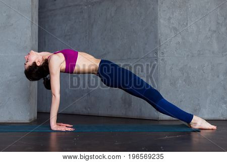 Pretty thin woman in sports bra and leggings doing yoga upward facing plank pose, purvottanasana, working out indoors.