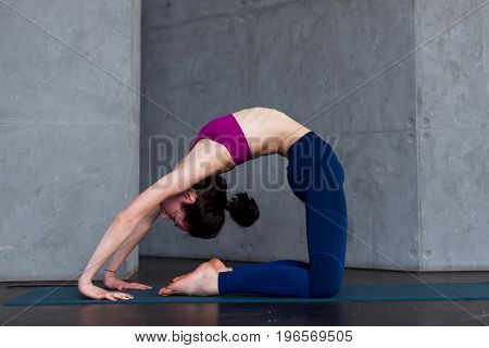 Skinny flexible female yogini bending backwards doing stretching exercises on floor in a room.