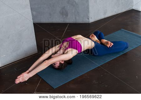 Young flexible woman stretching on mat lying on mat in fish pose with her legs crossed in lotus position.