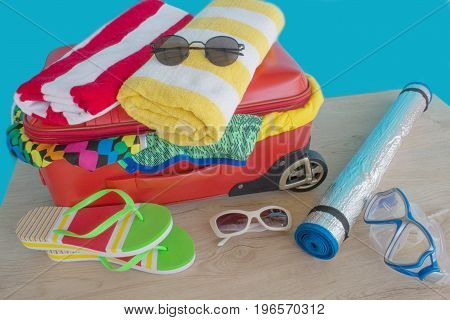 Opened traveler case Suitcase on table. Red Suitcase with different things prepared for travel