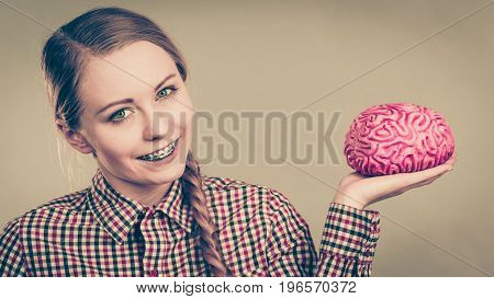 Intellectual expressions being focused concept. Closeup of attractive woman happy thinking face expression holding brain