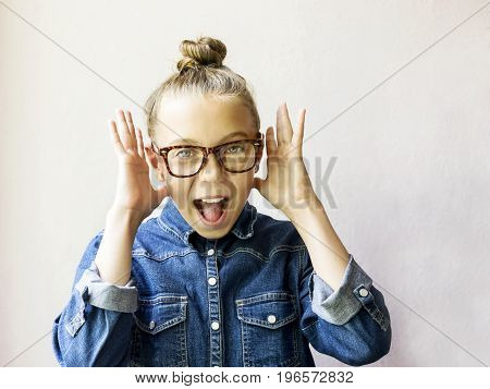 Surprised beautiful teen girl with glasses and jeans shirt on a light background