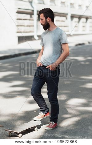 Street urban old school sport at summer. Hipster skateboarder and skate at the street. Journey for adult beard man