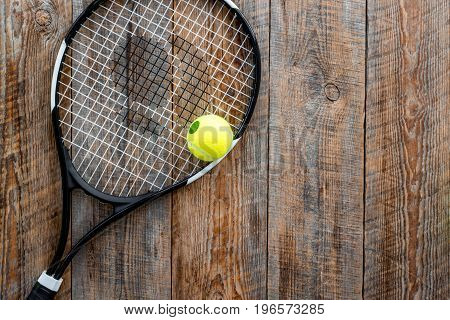 Sport background. Tennis balls and racket on wooden background top view.