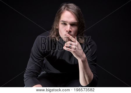 Portrait of puzzled brunette young man on black background