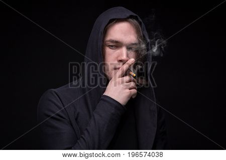 Smoking young man in the hood on black background
