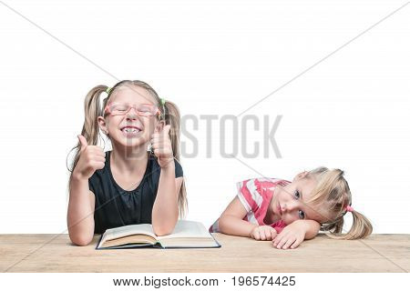 Two girls sitting at a table behind a book with different emotions isolated on a white background