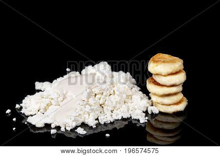 Pile of homemade cottage cheese sodden with sour cream, next to a pile of curd cakes isolated on a black background