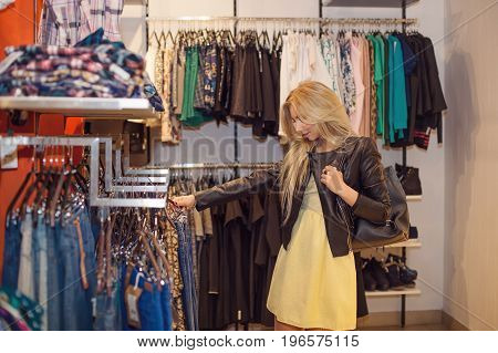 Concept Shopping. Portrait of beauty smiling woman in shop, choosing clothes. Indoor. Copy space