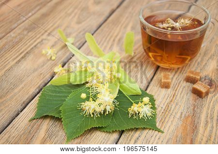 Blossoms of linden tree and linden tea on wooden background